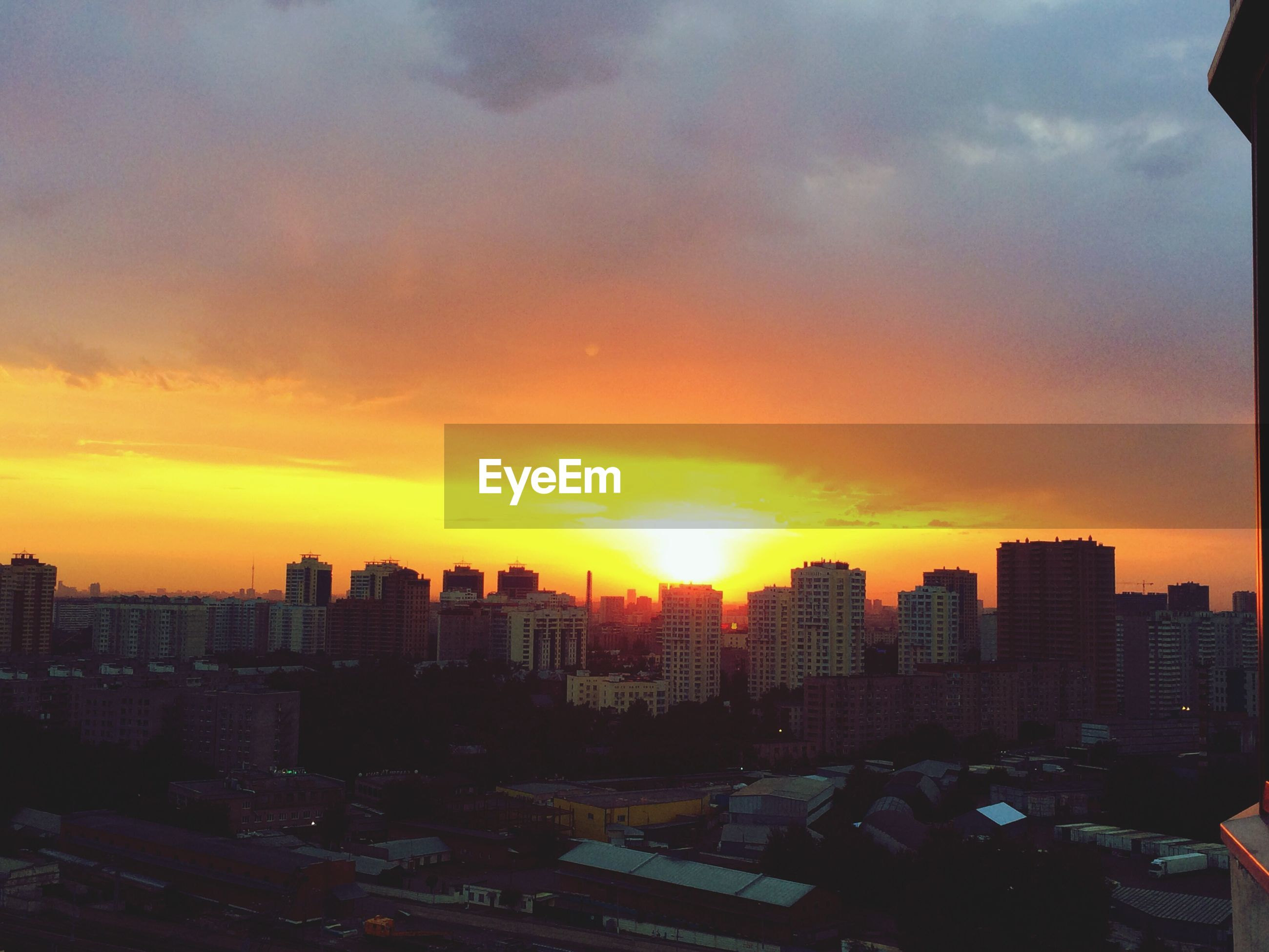 sunset, building exterior, architecture, city, built structure, cityscape, orange color, sky, cloud - sky, sun, high angle view, skyscraper, crowded, city life, residential building, residential district, silhouette, tall - high, sunlight, tower