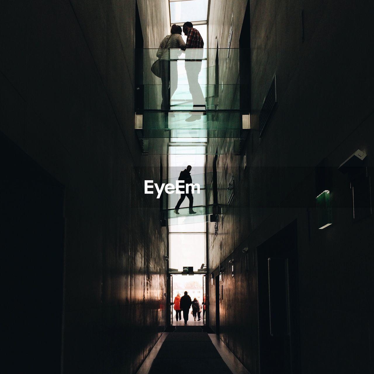 Silhouette of people walking in corridor