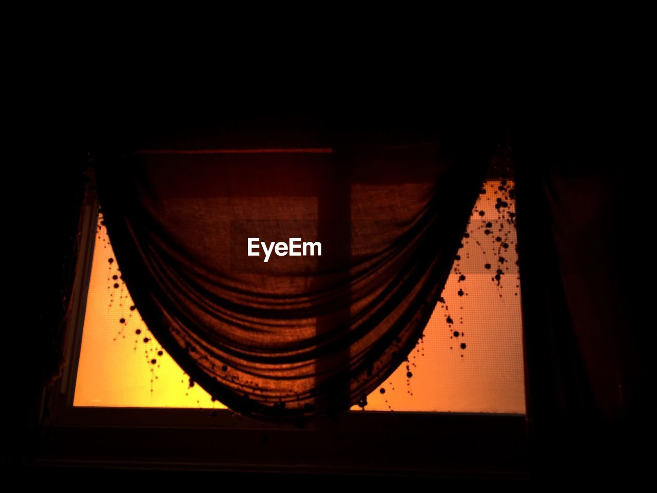 Low Angle View Of Window With Curtain During Sunset