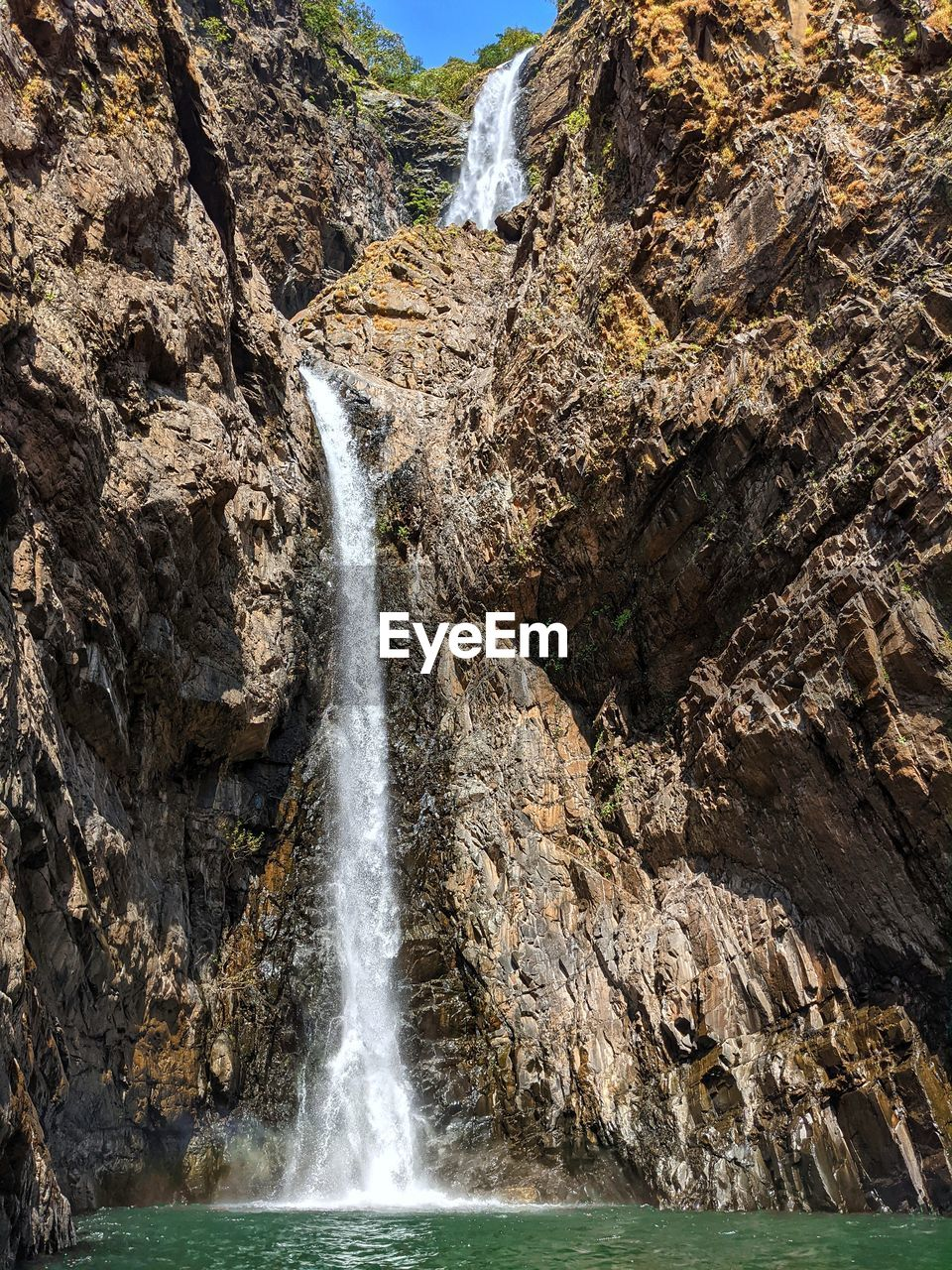 LOW ANGLE VIEW OF WATERFALL ON ROCK