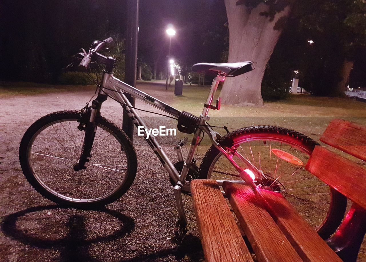 bicycle, night, mode of transport, transportation, land vehicle, illuminated, outdoors, no people, stationary, built structure, bicycle rack, building exterior, architecture, city, tree, nature
