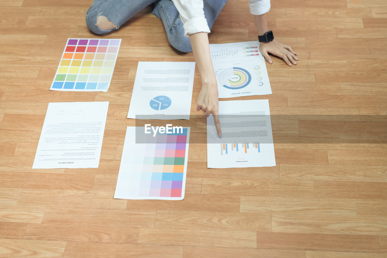 Midsection Of Woman Pointing On Graph Chart At Hardwood Floor