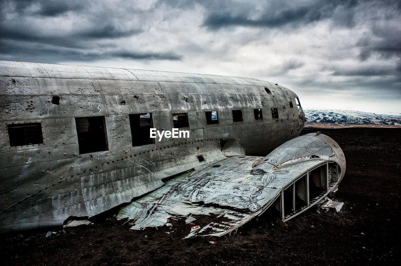 Crashed airplane on beach at solheimasandur against cloudy sky