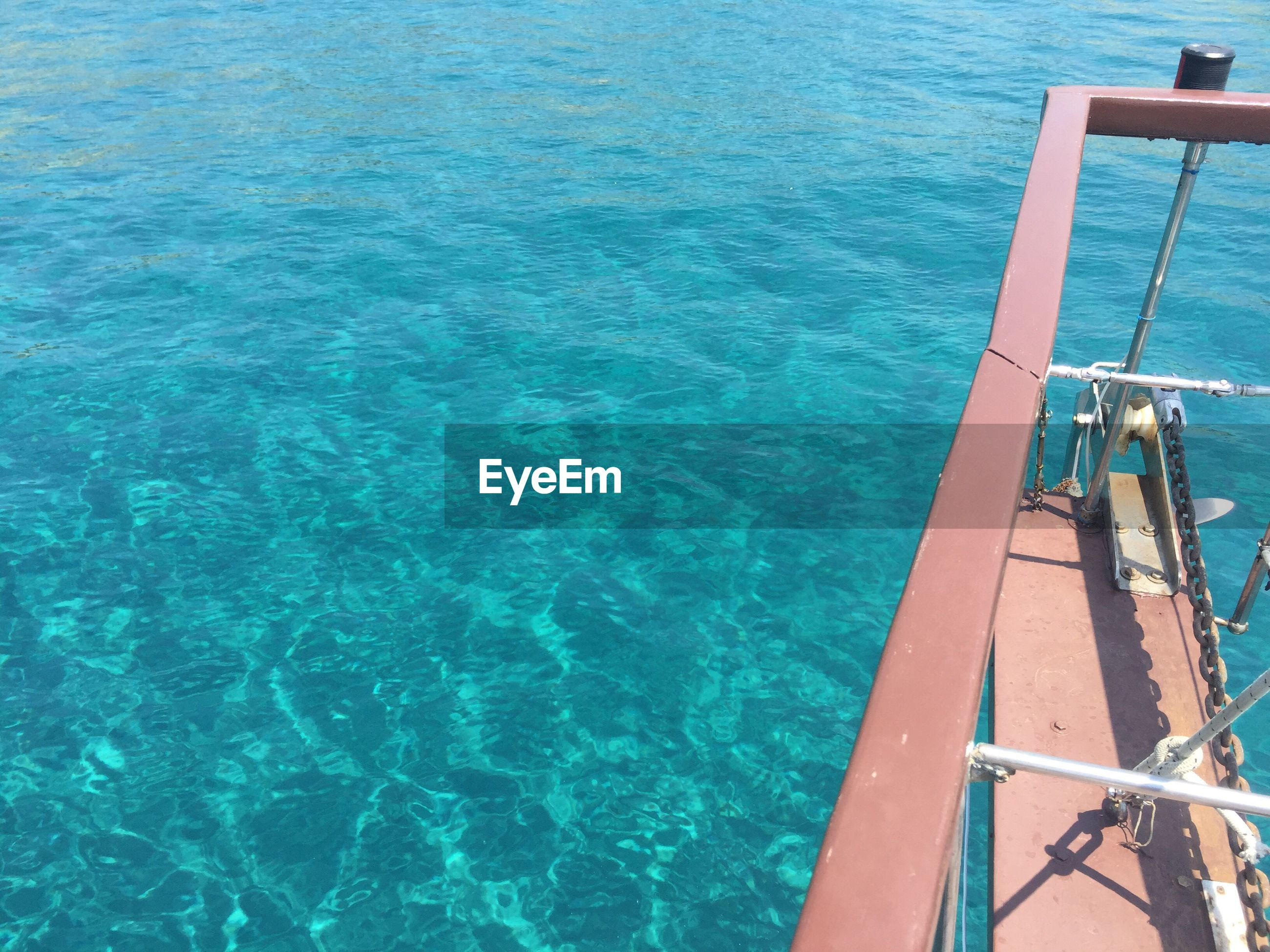 High angle view of pulley on metal structure over turquoise sea