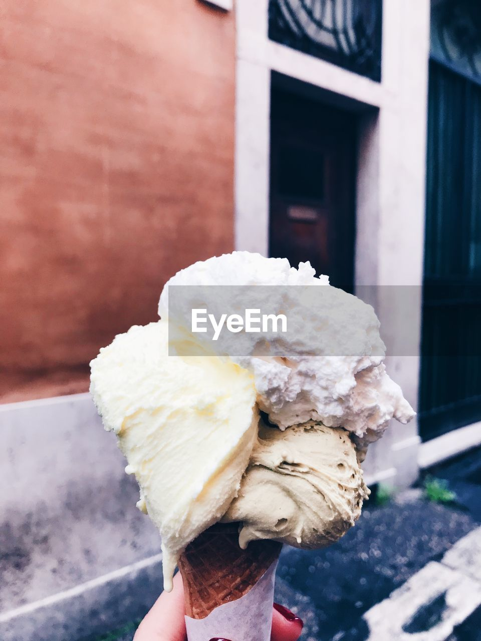 human body part, human hand, sweet food, holding, one person, hand, frozen, body part, sweet, ice cream, frozen food, real people, ice cream cone, food, unrecognizable person, unhealthy eating, food and drink, personal perspective, indulgence, cone, temptation, finger, outdoors, human limb
