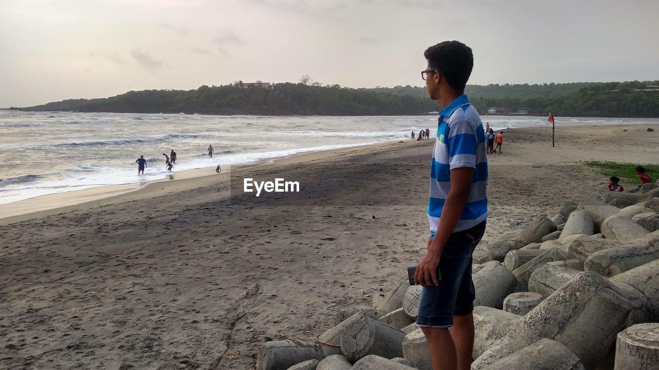 FULL LENGTH OF MAN SITTING ON BEACH AGAINST SKY