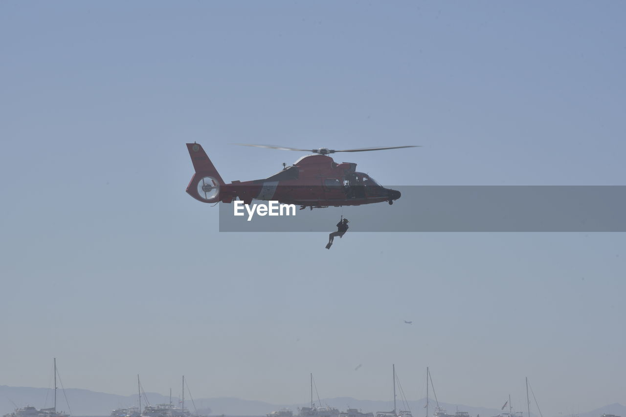 sky, flying, transportation, air vehicle, mode of transportation, mid-air, on the move, airplane, motion, clear sky, nature, helicopter, no people, military, travel, day, outdoors, copy space, low angle view, blue, aerospace industry, government, plane