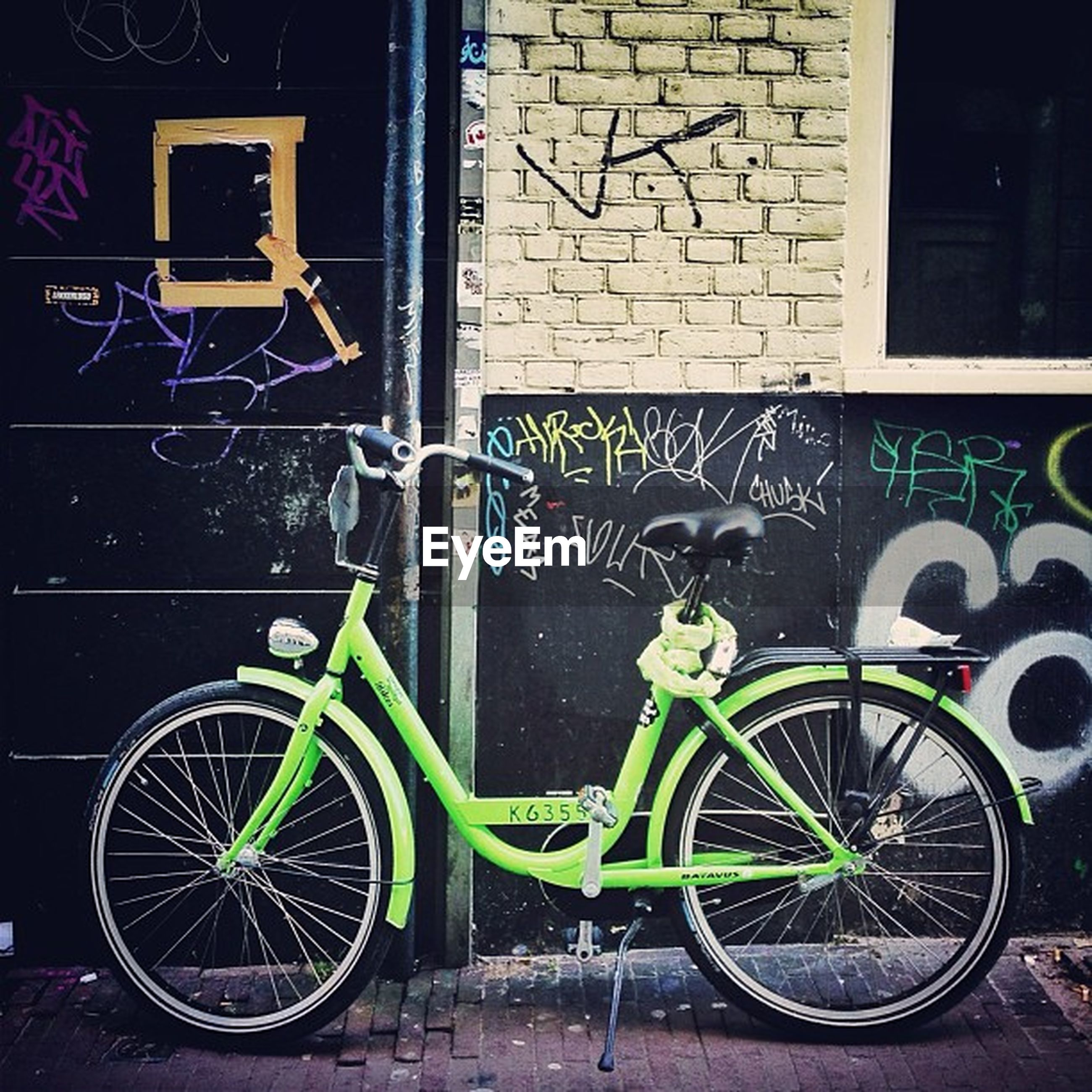 bicycle, transportation, mode of transport, land vehicle, stationary, parking, parked, building exterior, wall - building feature, architecture, built structure, leaning, wheel, street, wall, cycle, outdoors, graffiti, day, no people
