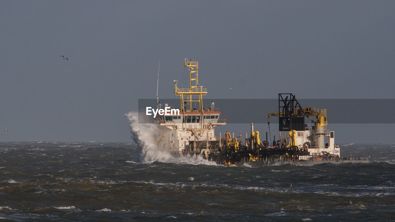 sea, water, motion, sky, nature, nautical vessel, waterfront, wave, no people, ship, outdoors, transportation, industry, mode of transportation, environment, beauty in nature, copy space, built structure, clear sky, power in nature