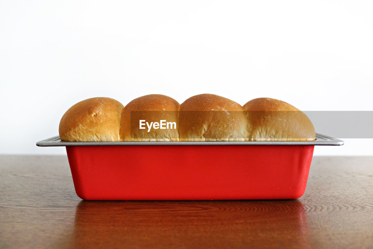 Close-up of homemade bread loaf in baking tray on wooden table against white background