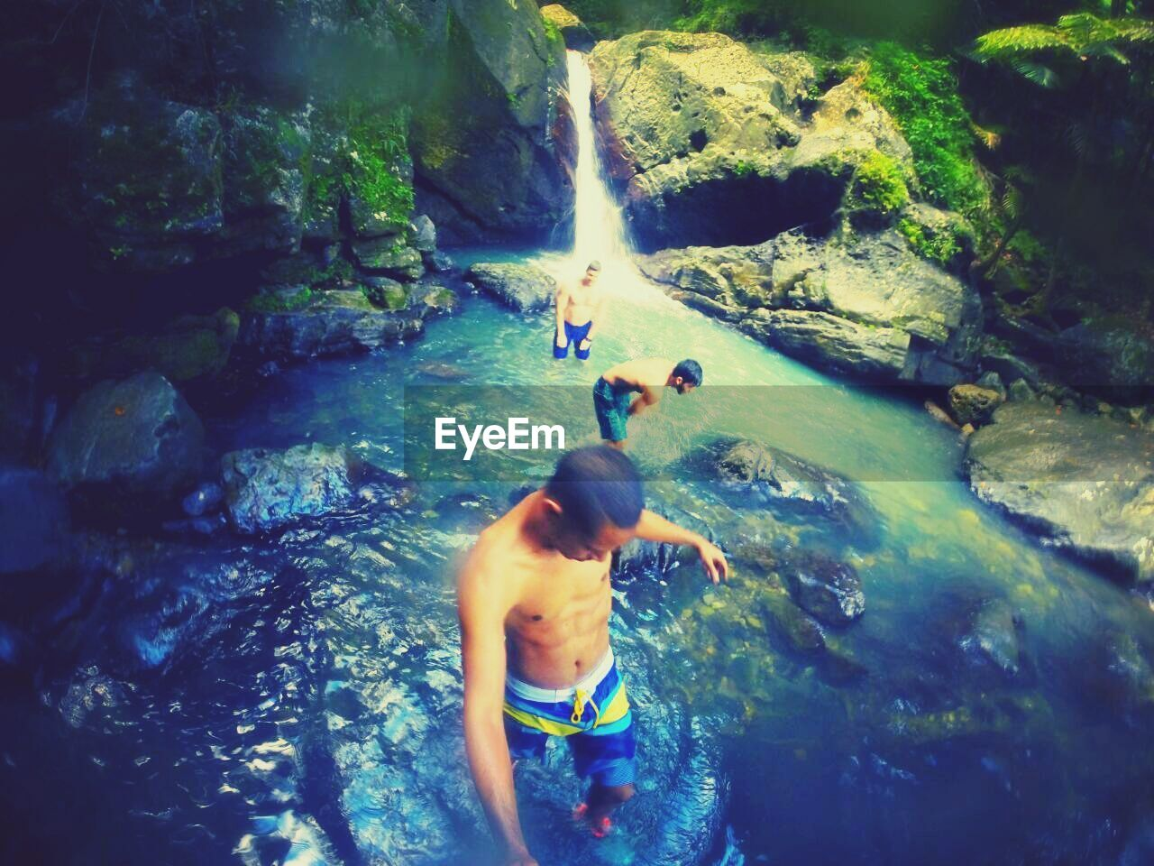 water, shirtless, waterfall, rock - object, real people, high angle view, river, motion, leisure activity, day, one person, adventure, nature, vacations, men, outdoors, lifestyles, standing, swimming, full length, beauty in nature, young adult, adult, people