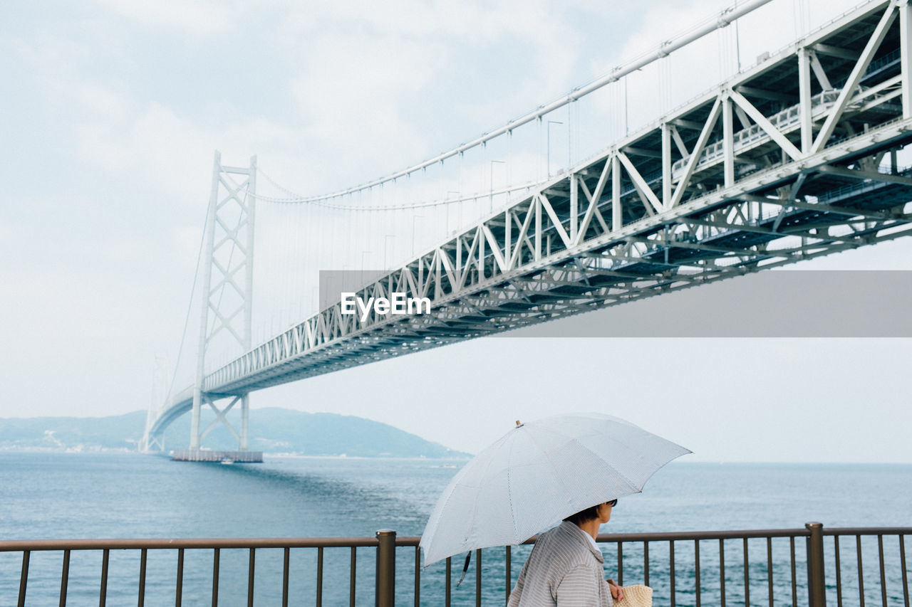 bridge - man made structure, connection, water, sky, transportation, suspension bridge, outdoors, sea, real people, day, architecture, one person, nature, cloud - sky, built structure, women, bridge, below, travel destinations, beauty in nature, under, people