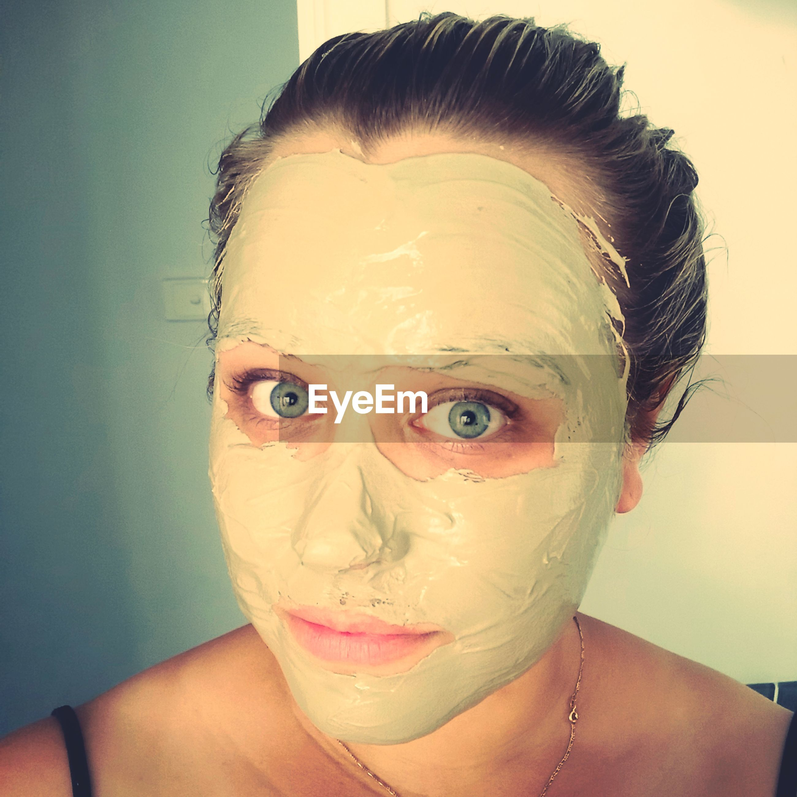 Close-up portrait of young woman with facial mask at home