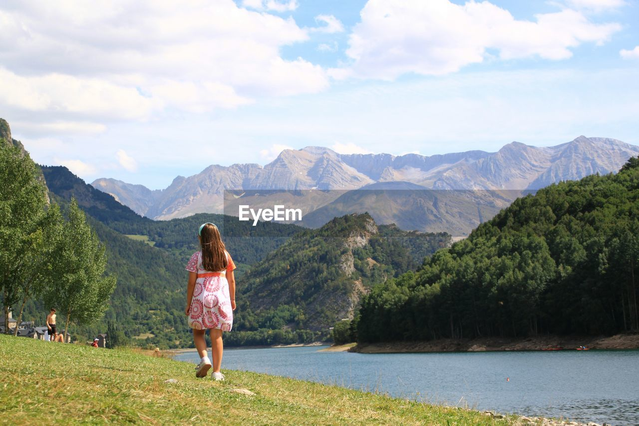 Rear View Of Young Girl Walking By Lake Against Mountains