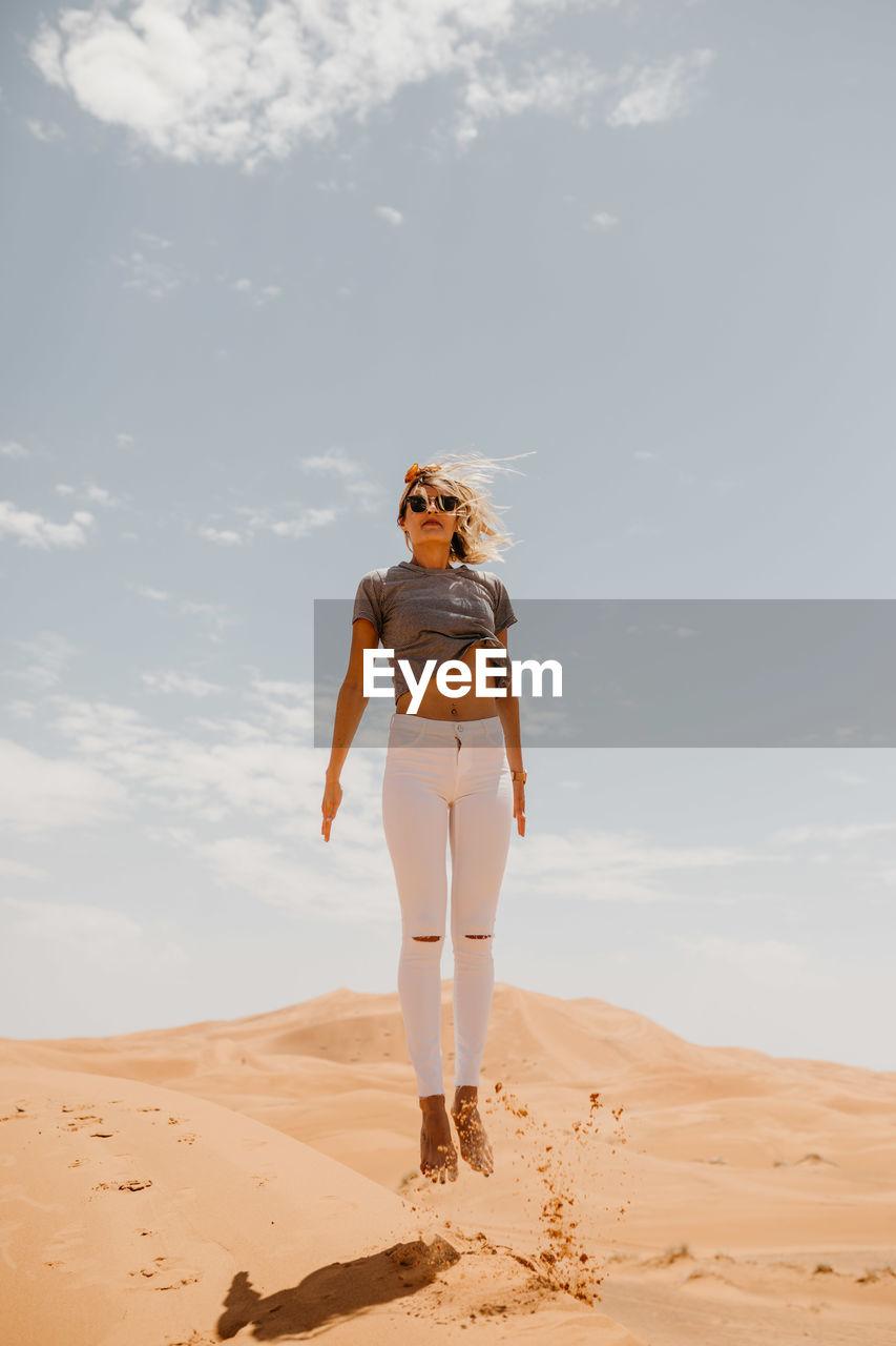 Woman Levitating Over Desert In Sunny Day