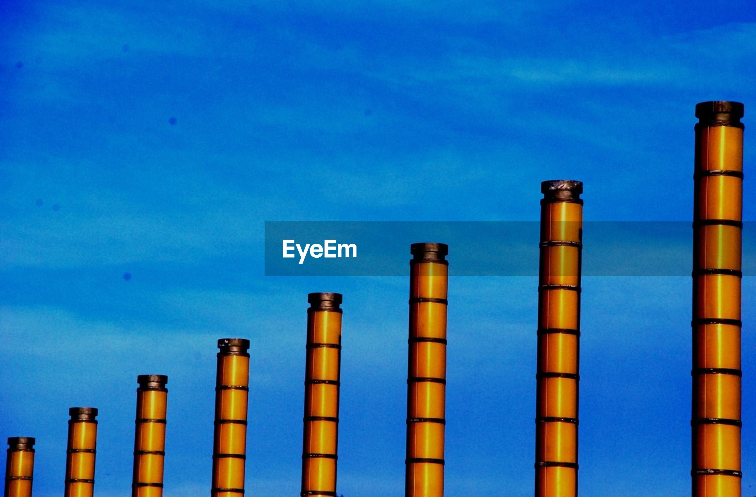 blue, in a row, low angle view, architecture, built structure, sky, side by side, building exterior, wooden post, pole, industry, no people, tall - high, outdoors, copy space, smoke stack, repetition, day, nature, wood - material