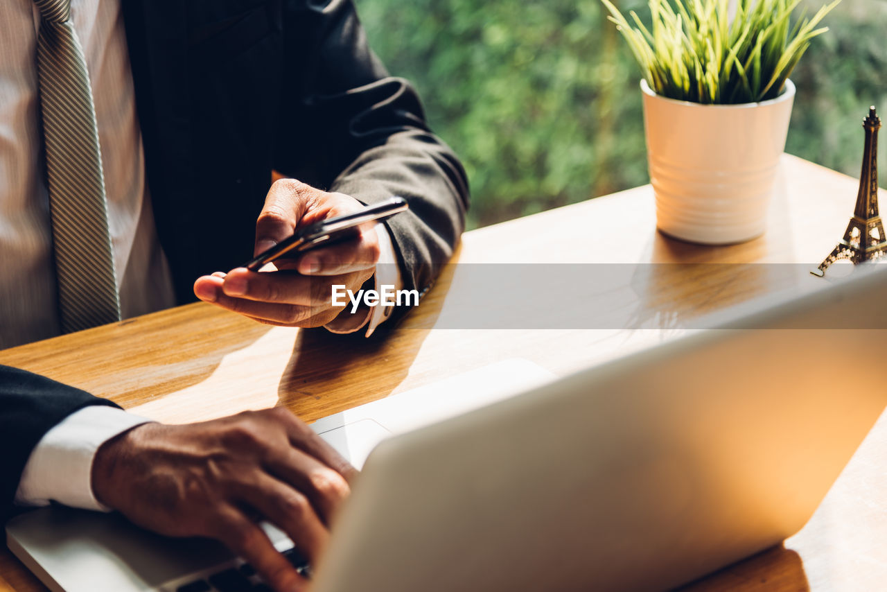 Midsection of businessman using laptop at table