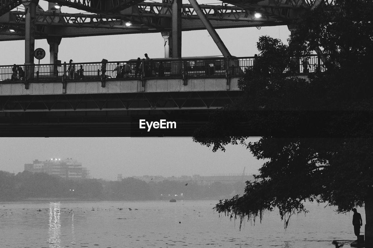 bridge - man made structure, water, river, connection, tree, transportation, architecture, built structure, day, sky, outdoors, bridge, nature, men, nautical vessel, city, people