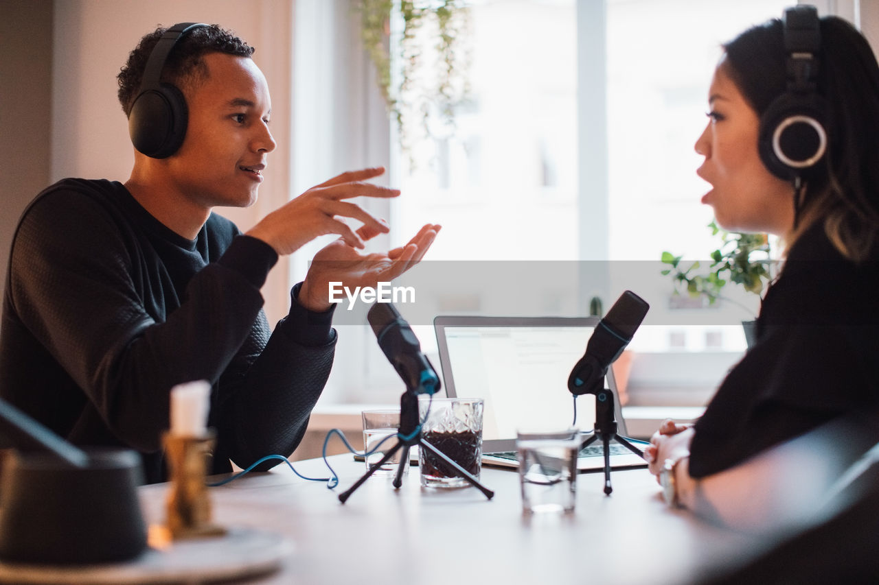 Male blogger gesturing to female wearing headphones sitting at table