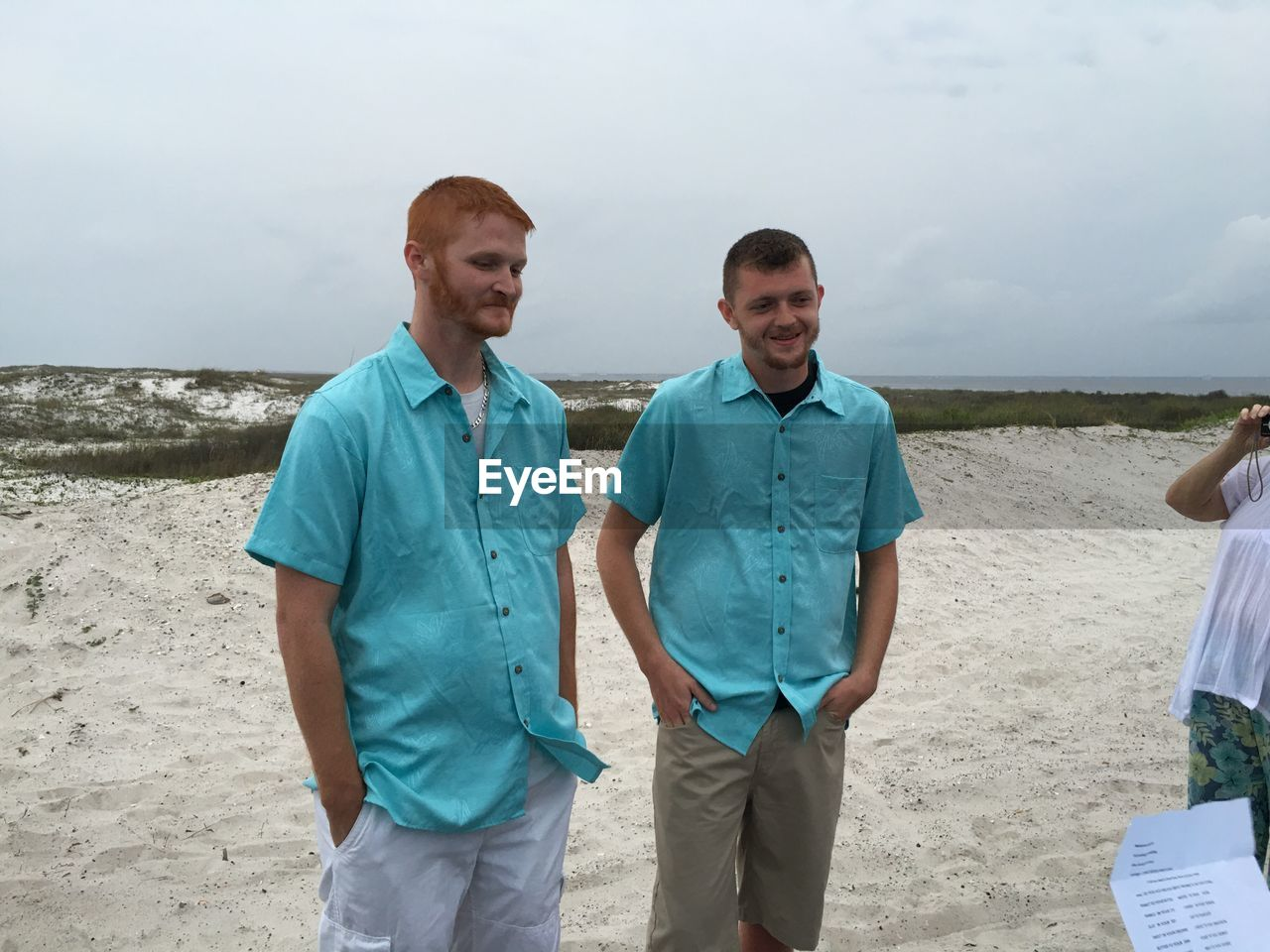Smiling friends wearing blue shirt standing at beach against sky