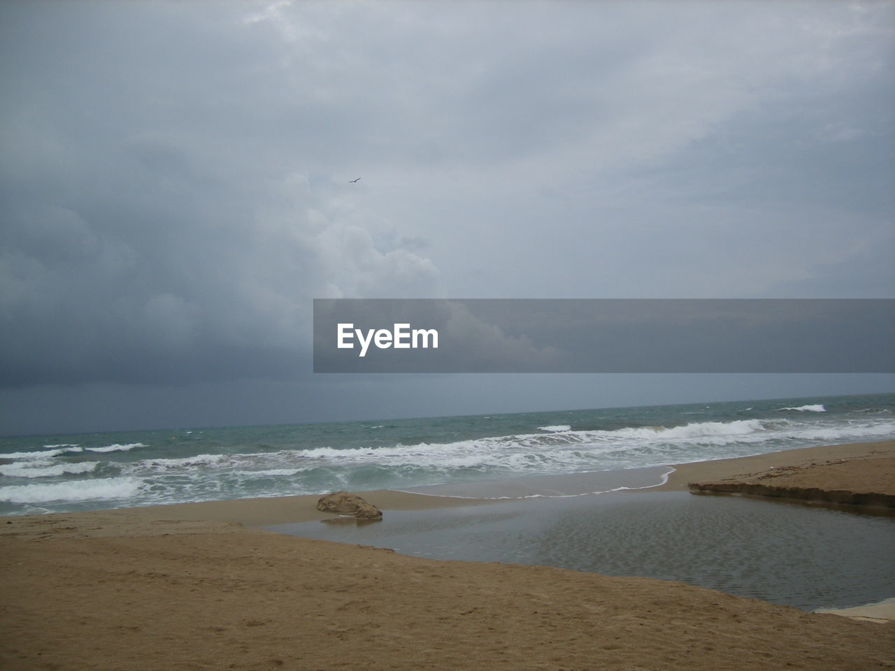 Scenic view of beach by sea against cloudy sky