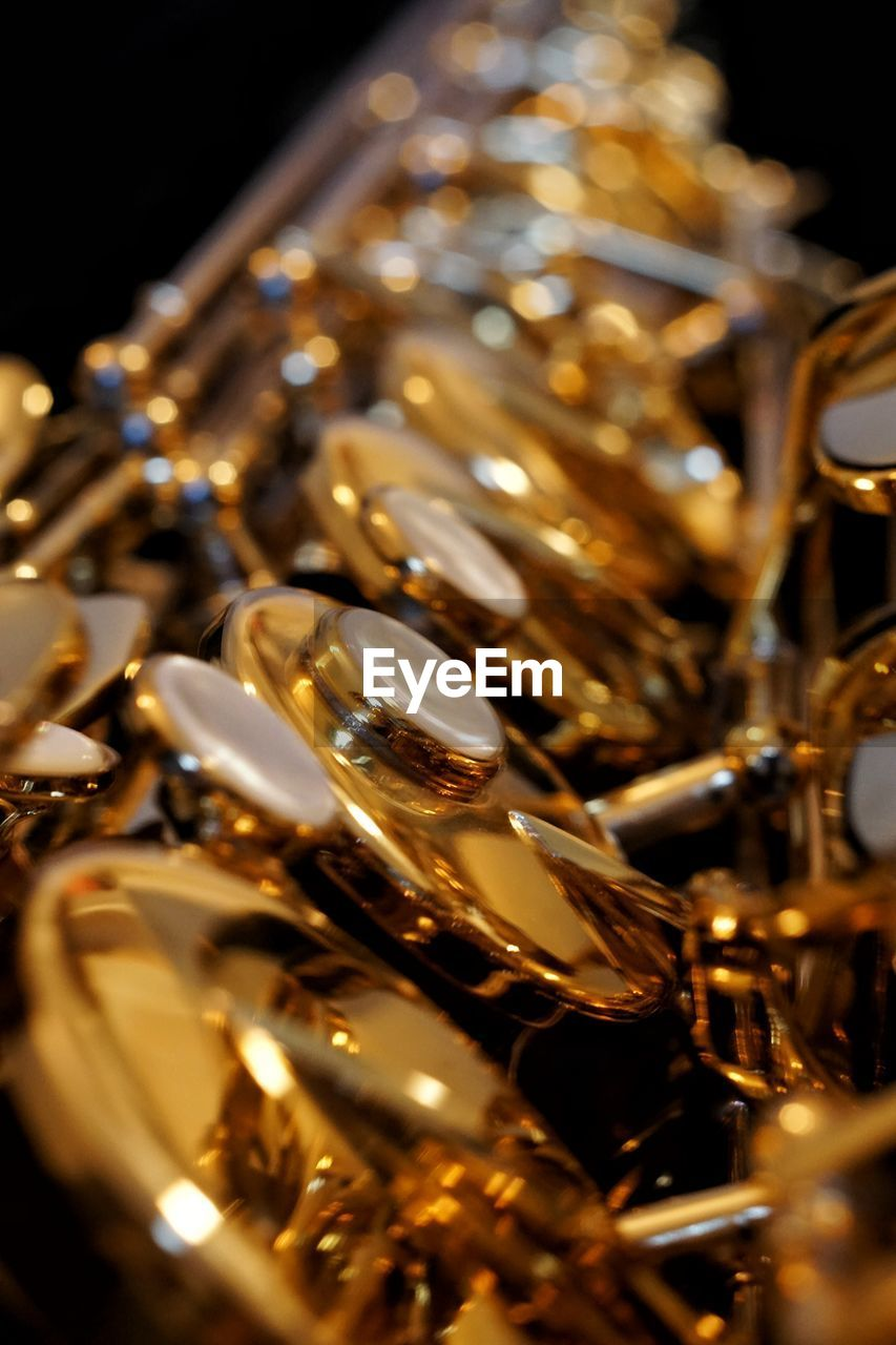 gold colored, shiny, gold, selective focus, no people, music, close-up, large group of objects, musical instrument, indoors, black background, wind instrument, day