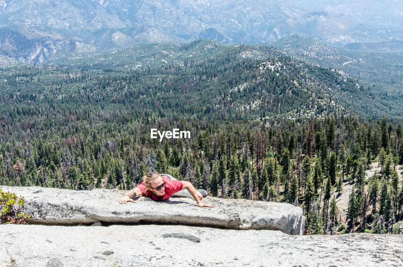 Man climbing mountain in forest