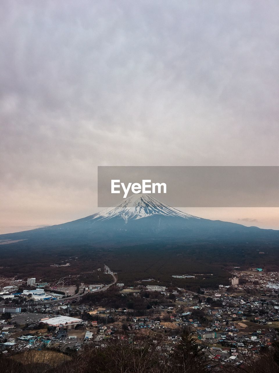 Aerial View Of City And Mt Fuji Against Cloudy Sky