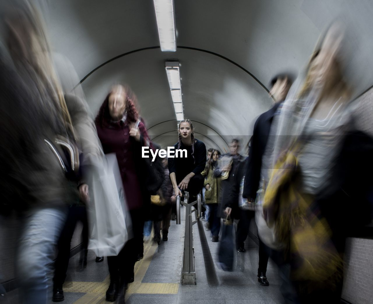 Portrait Of Woman Sitting On Railing At Subway Station