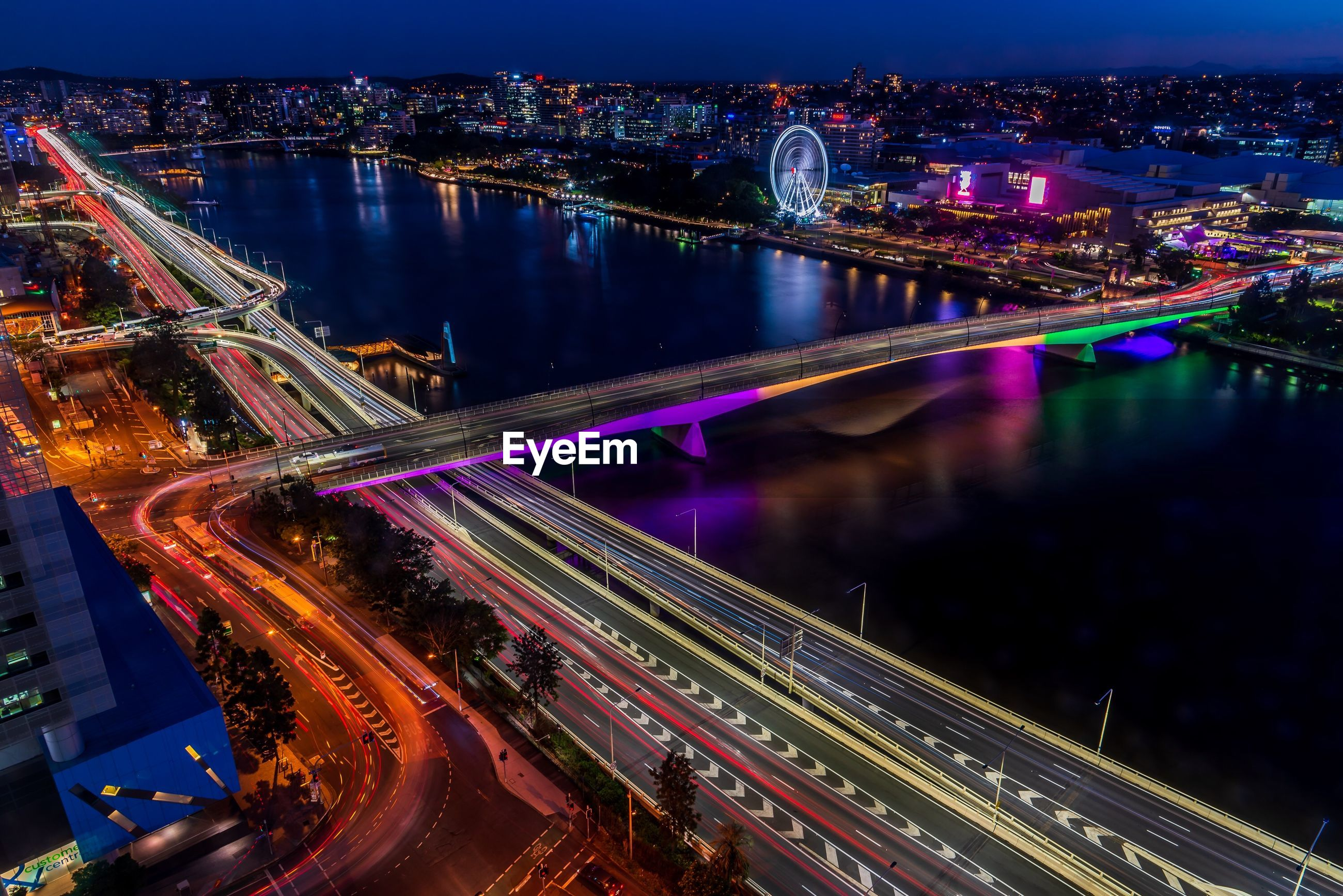 Aerial view of illuminated light trails on bridge in city at night