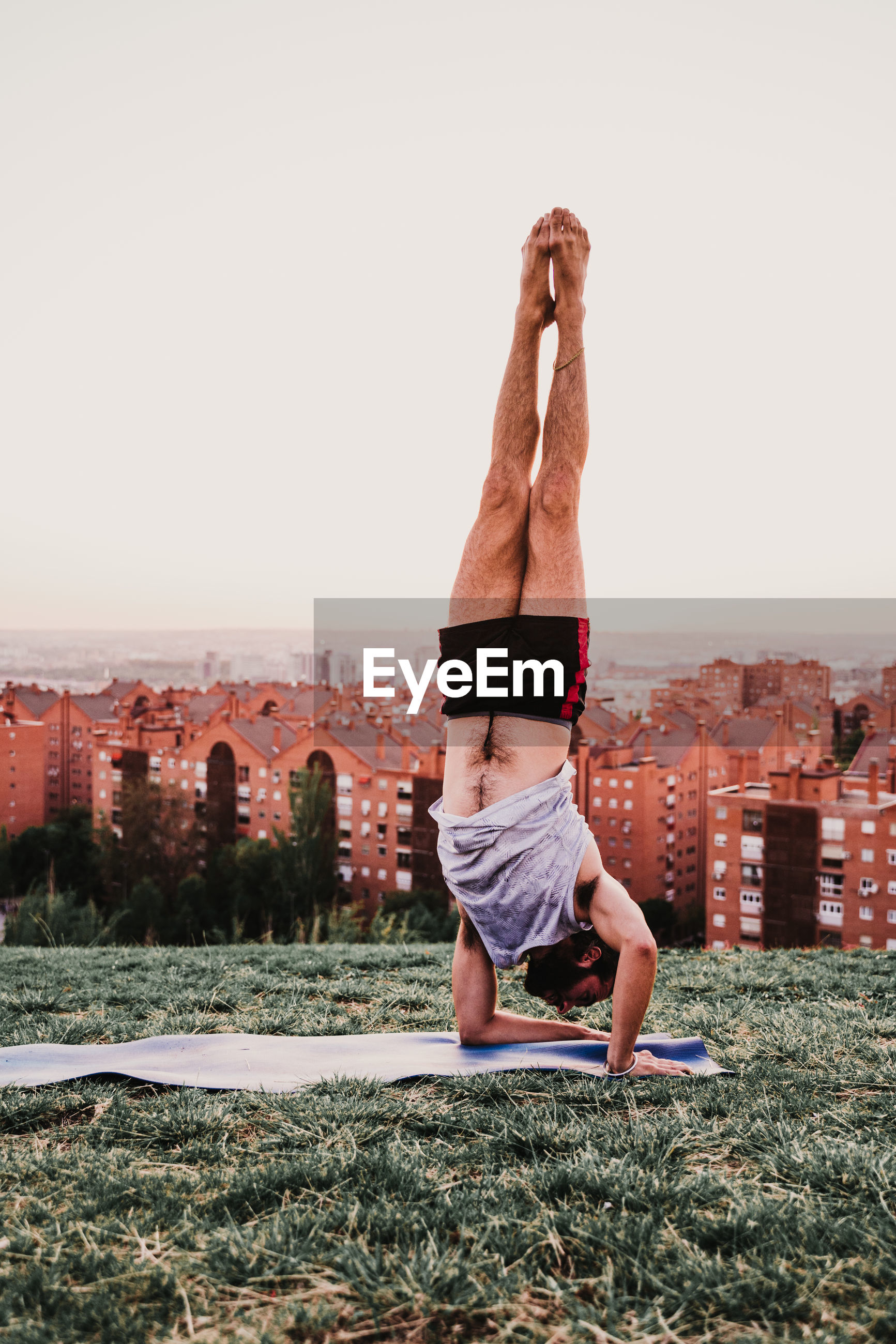 Full length of man with arms raised doing handstand over mat on grass against clear sky