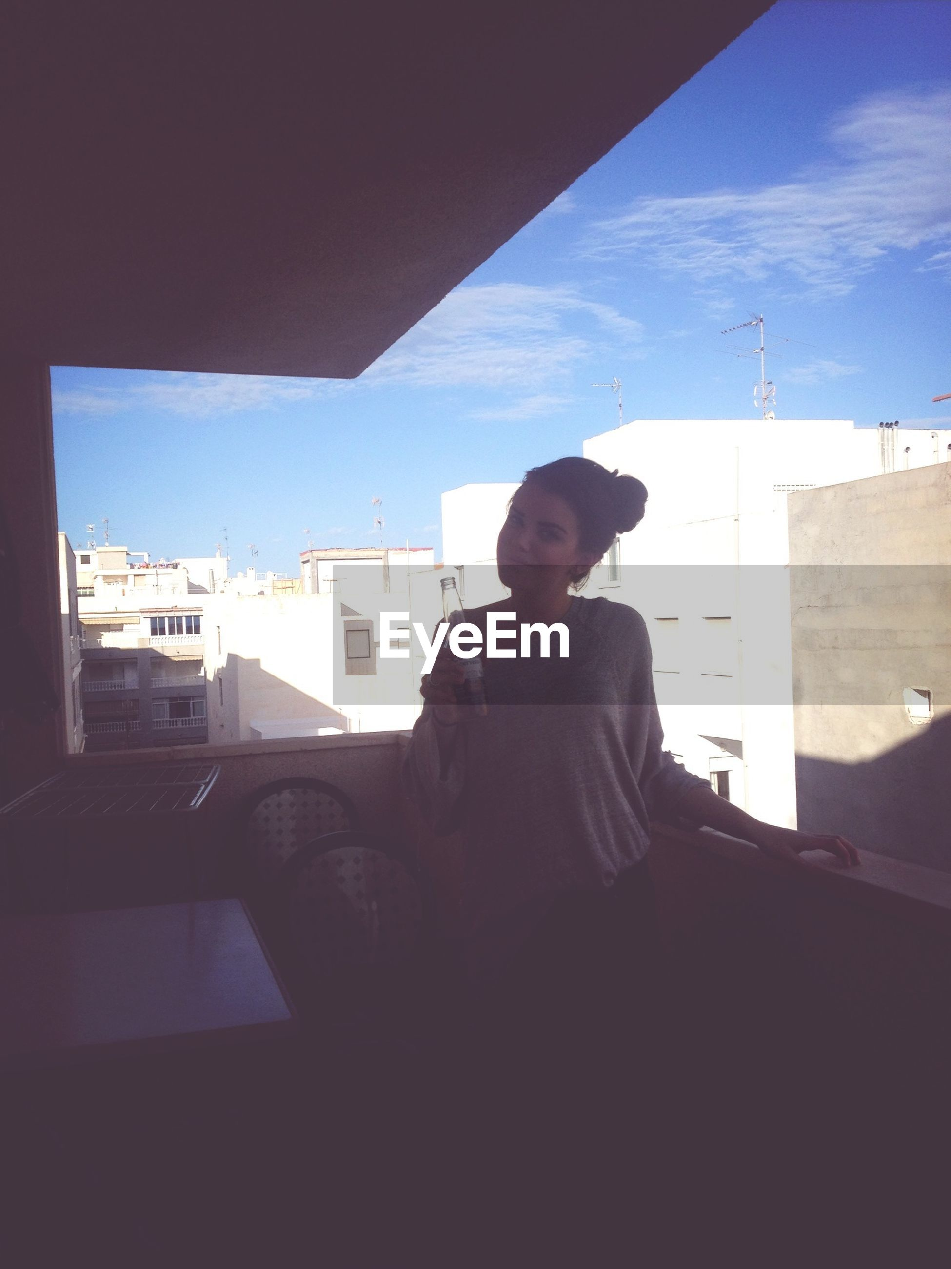 lifestyles, architecture, built structure, young men, casual clothing, leisure activity, young adult, person, building exterior, indoors, sky, waist up, sitting, standing, three quarter length, sunlight, communication, window