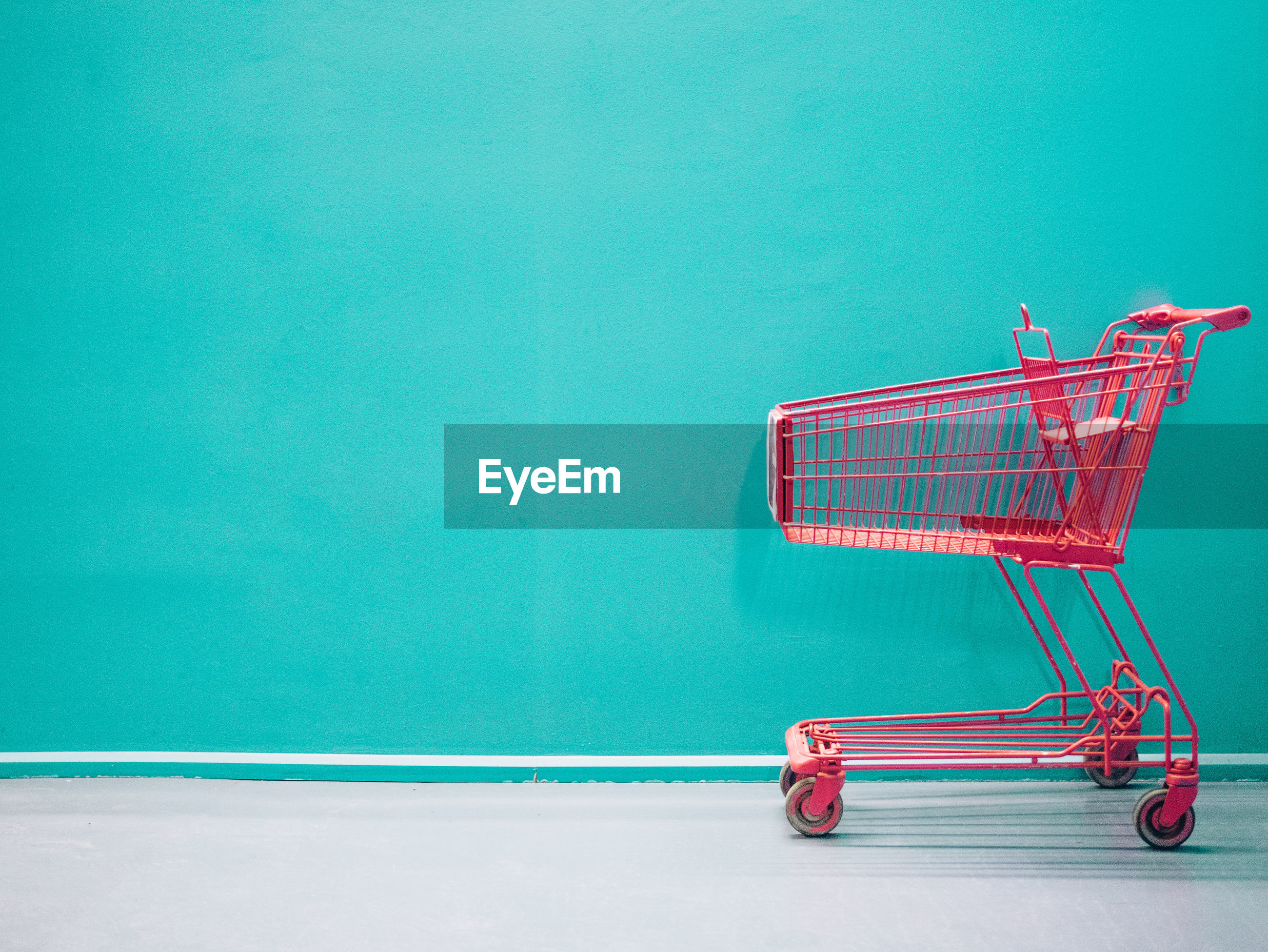 Empty shopping cart against turquoise colored wall