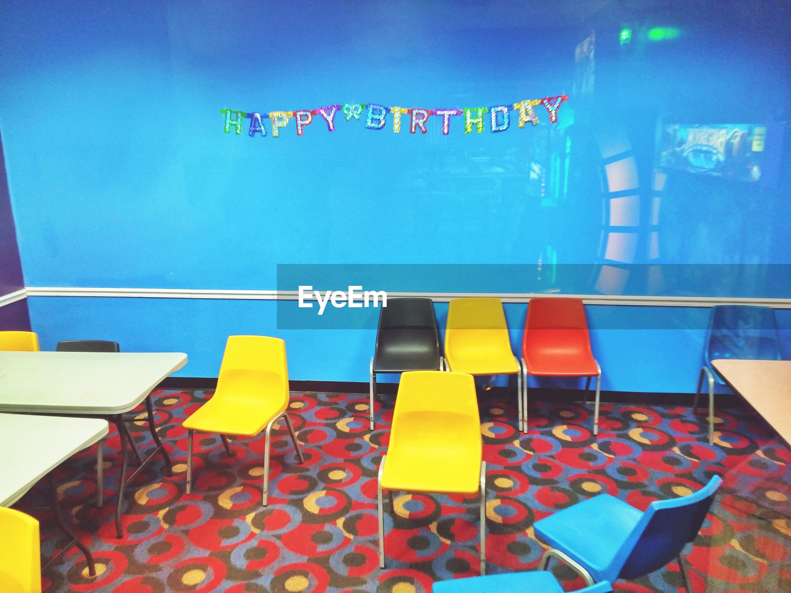 text, western script, communication, blue, chair, indoors, built structure, absence, multi colored, architecture, yellow, empty, information sign, no people, sunlight, wall - building feature, day, sign, flag, table