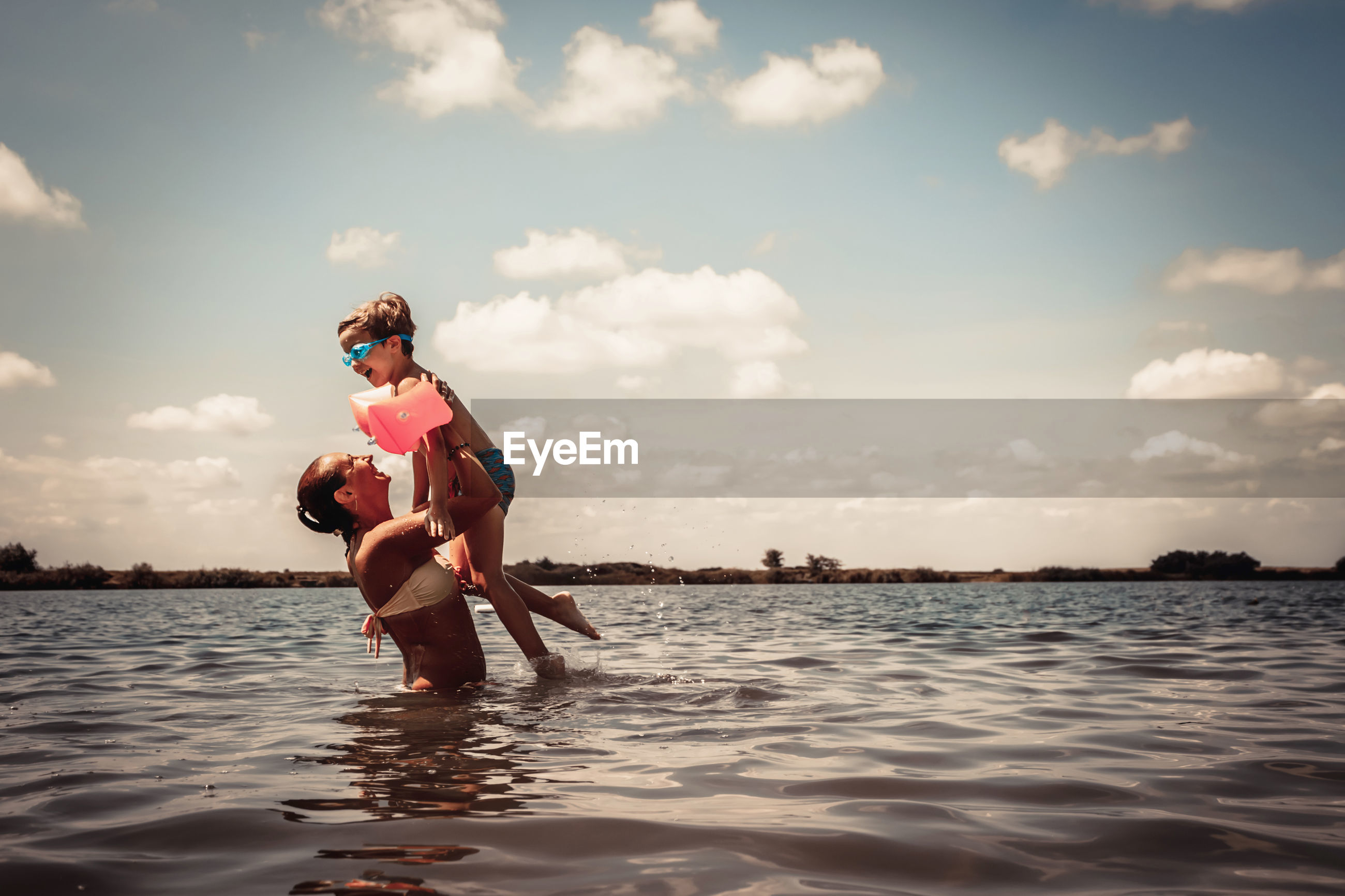Cheerful mother and son having fun in the water in summer day.