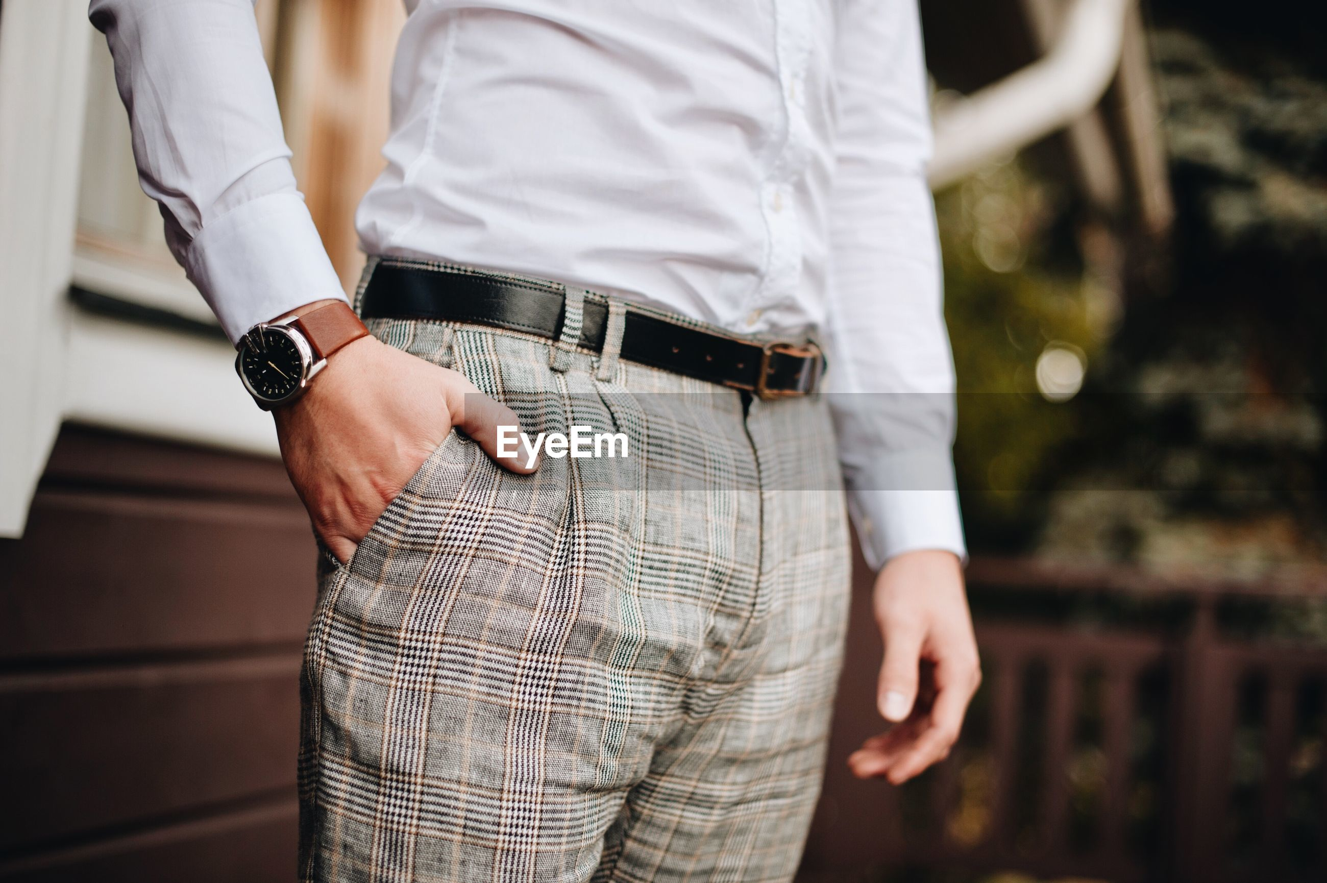 Midsection of well-dressed man standing in park