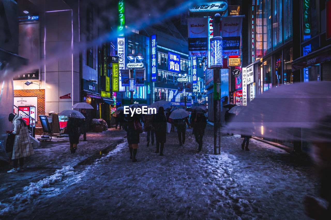 city, architecture, building exterior, built structure, illuminated, night, street, real people, city life, group of people, walking, men, large group of people, lifestyles, transportation, women, leisure activity, crowd, outdoors, rain