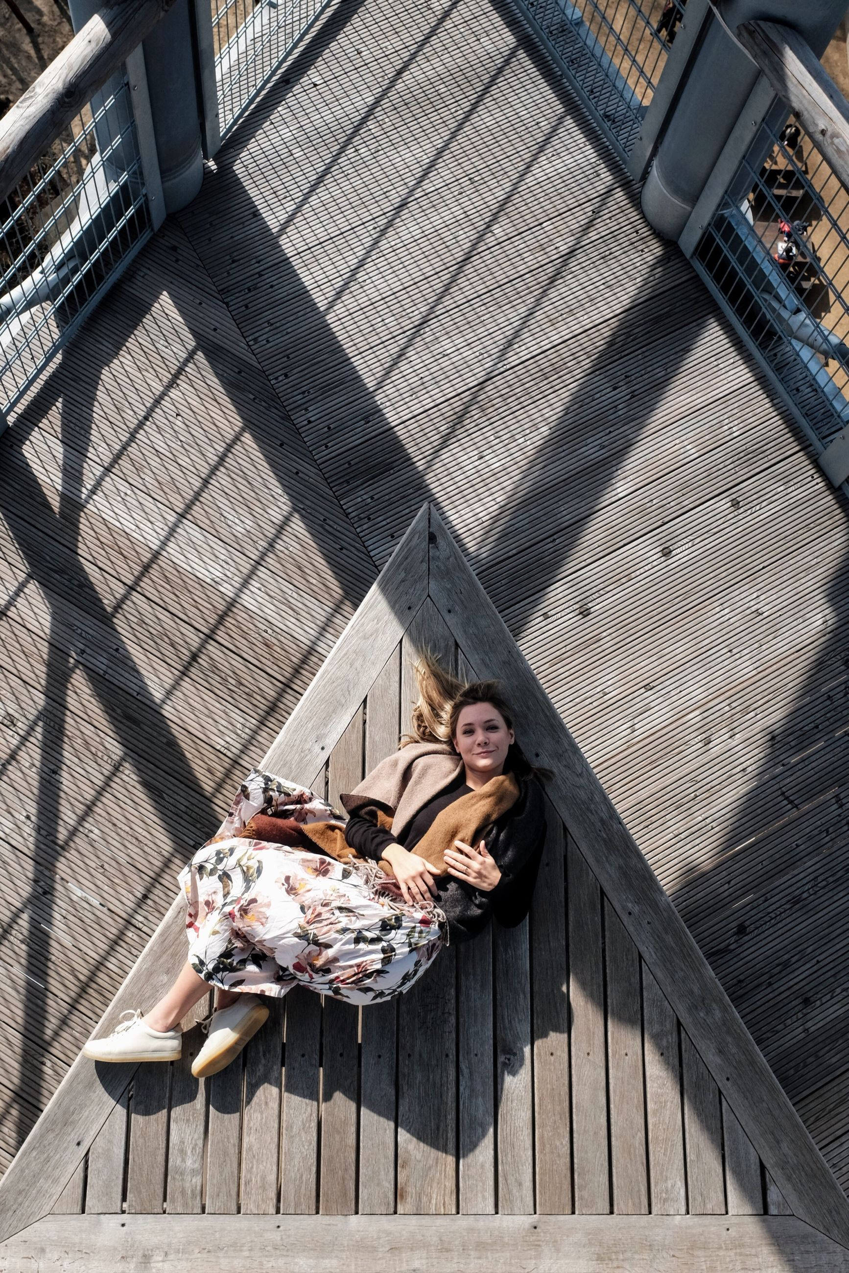 High angle view of woman lying on wooden terrace