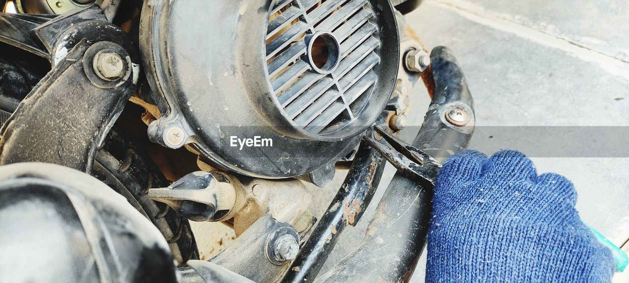 Cropped hand of mechanic repairing motor cycle
