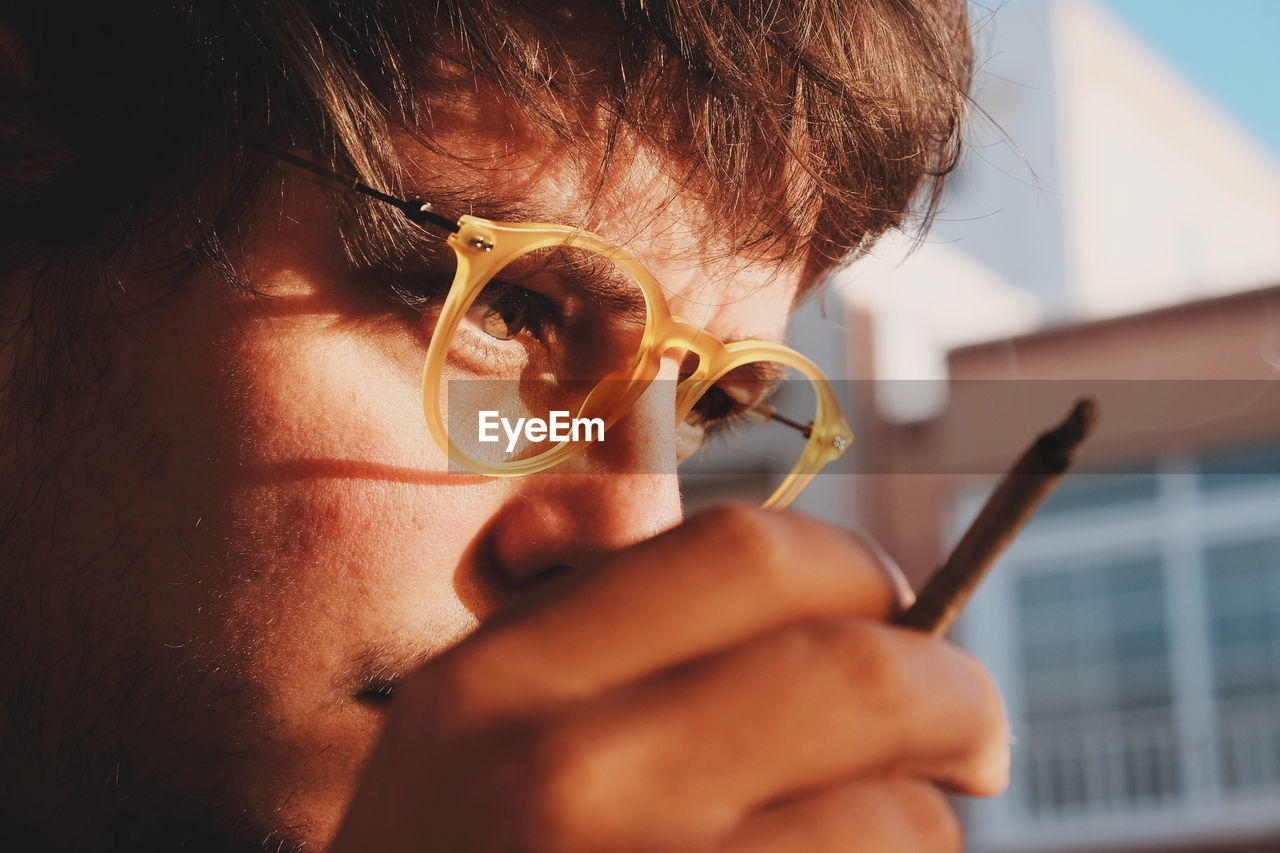 Close-Up Of Man Wearing Eyeglasses Holding Joint