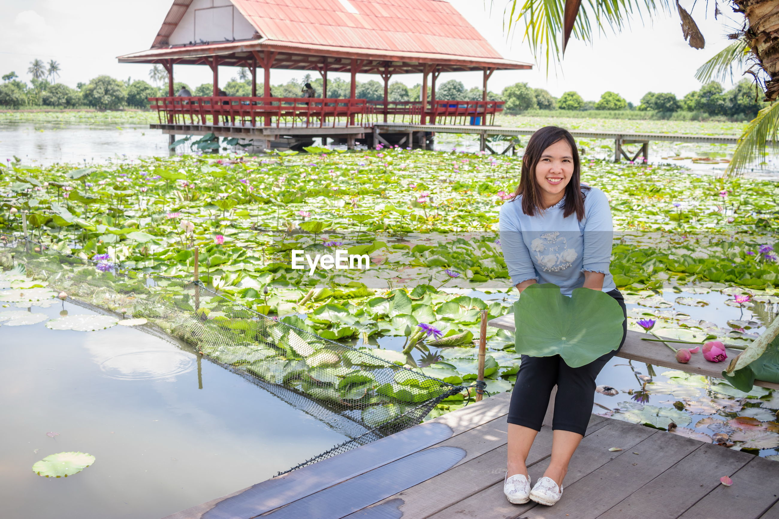 Portrait of smiling woman holding leaf while sitting by plants in lake