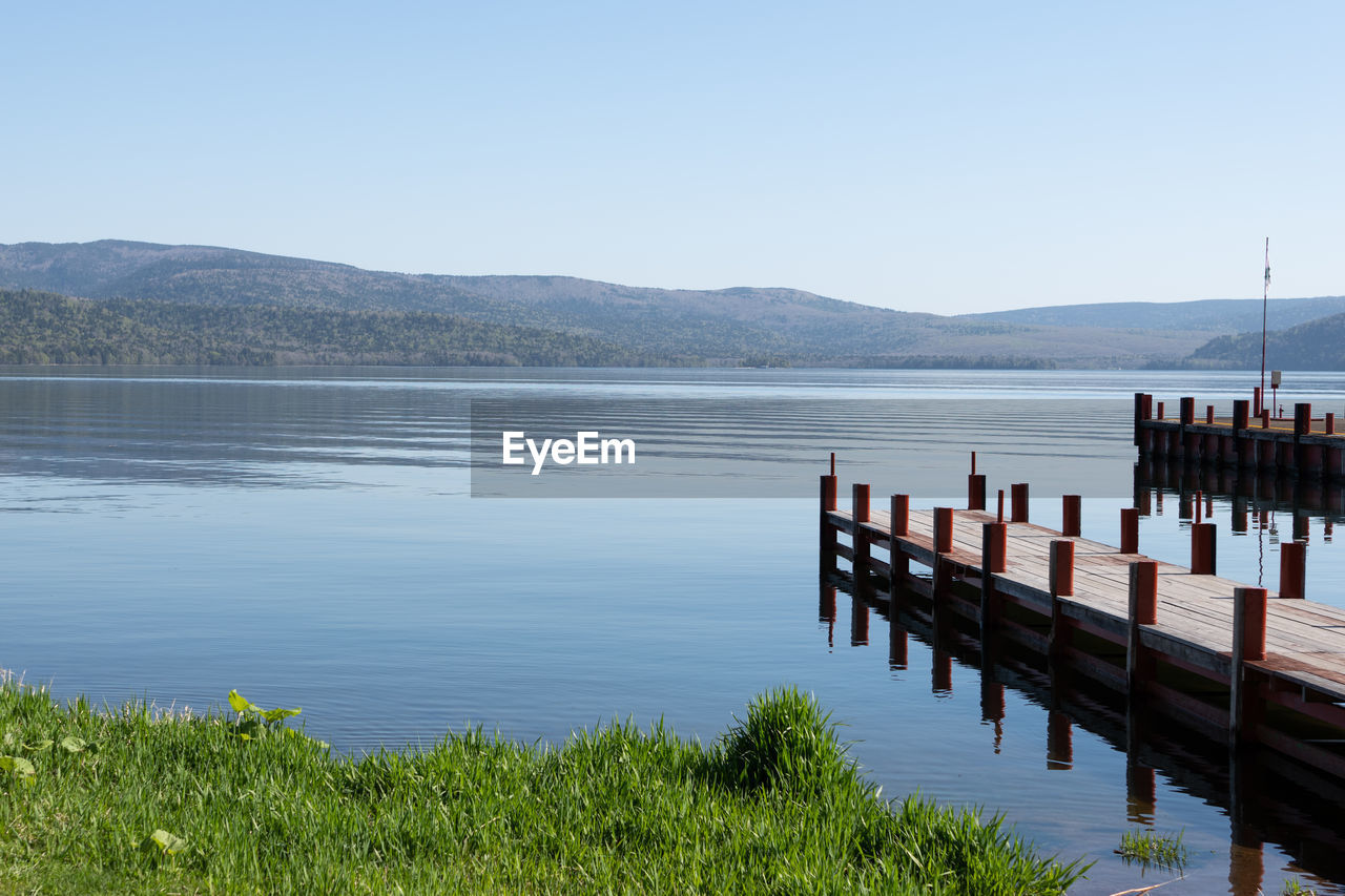 water, sky, scenics - nature, tranquility, tranquil scene, mountain, beauty in nature, lake, day, plant, nature, mountain range, no people, non-urban scene, clear sky, copy space, idyllic, grass, wood - material, outdoors, wooden post