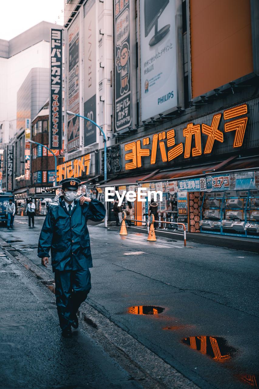 Man In Uniform Walking On Road By Buildings In City