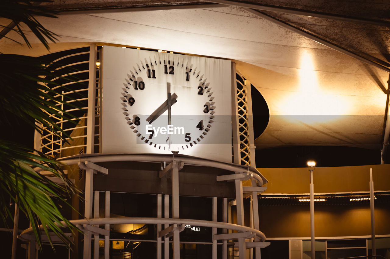 clock, time, low angle view, indoors, no people, illuminated, clock face, number, minute hand, architecture, night, hanging, accuracy, instrument of time, clock hand, table, shape, built structure, ceiling