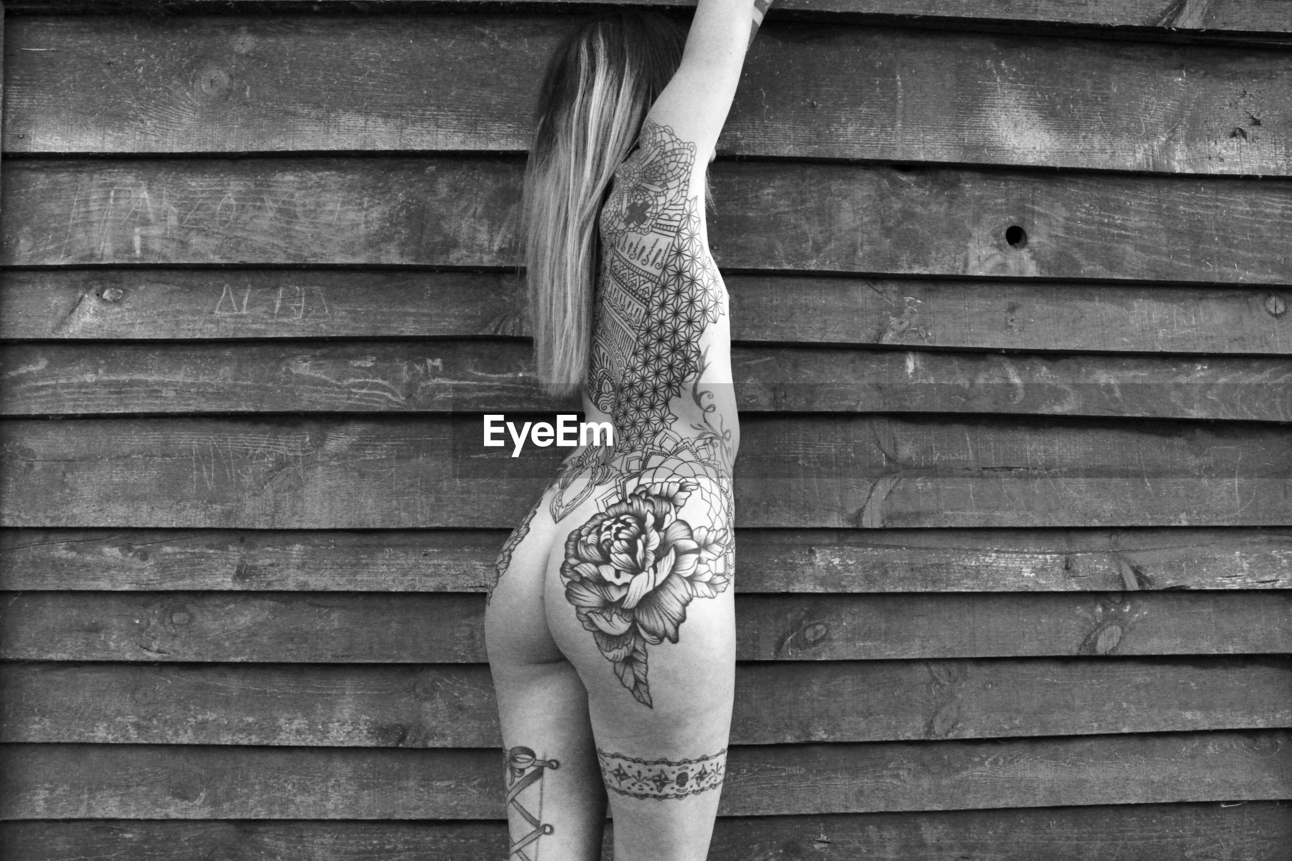 Rear view of naked tattooed woman against wall