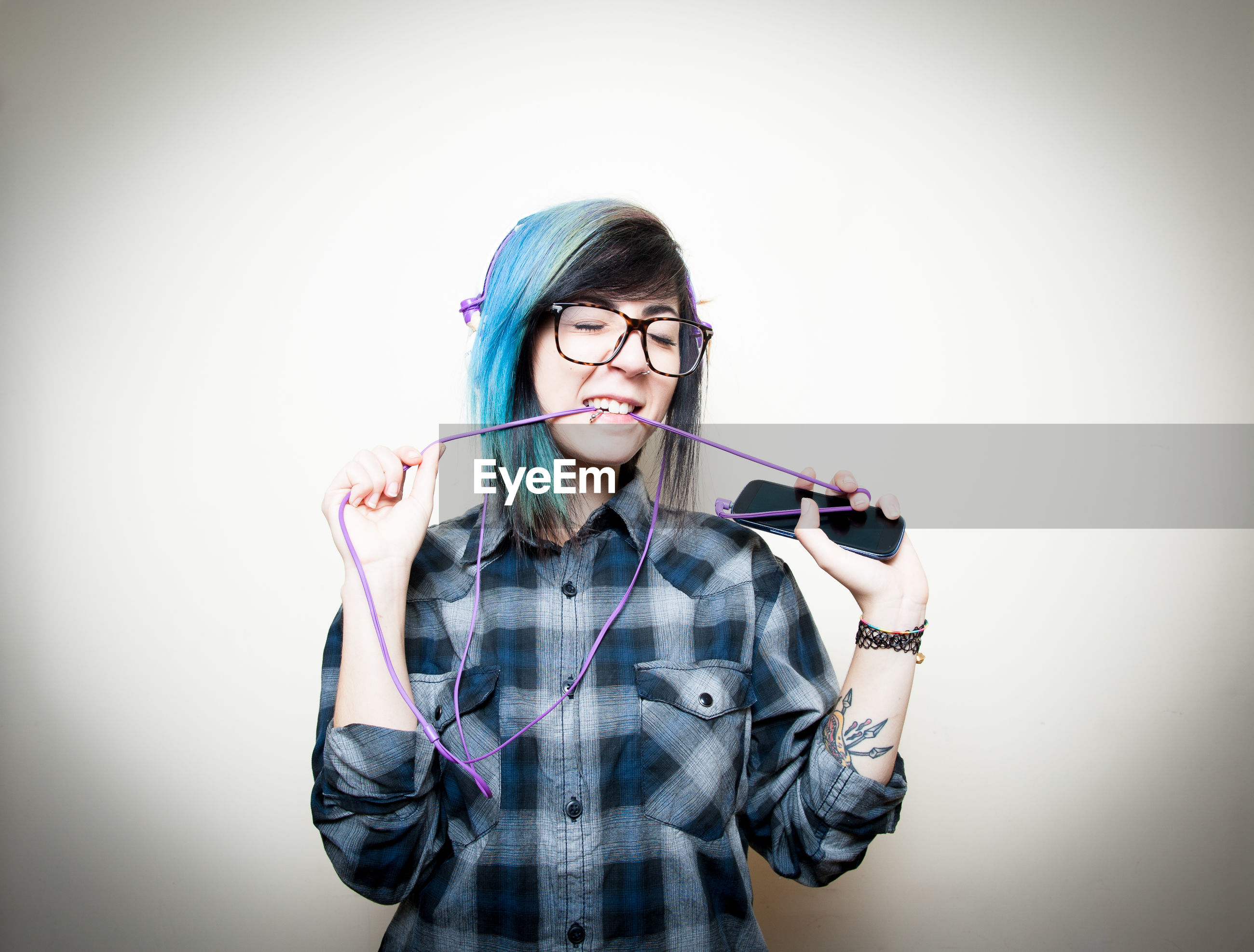 Young hipster biting headphones holding mobile phone against white background