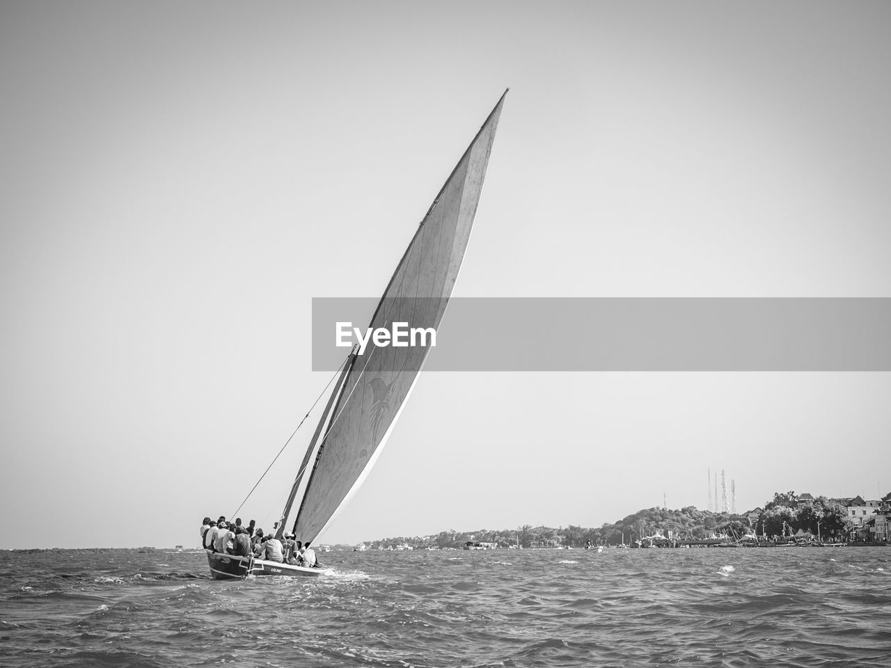 water, nautical vessel, sea, sky, mode of transportation, transportation, sailboat, waterfront, sailing, nature, day, clear sky, copy space, motion, outdoors, incidental people, beauty in nature, pole, yacht, yachting