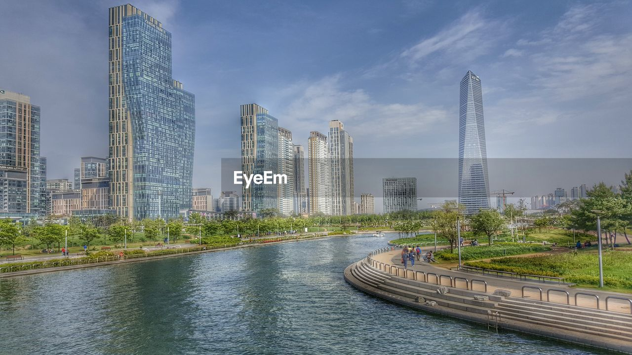 architecture, skyscraper, built structure, city, building exterior, modern, tower, river, sky, urban skyline, waterfront, cityscape, day, outdoors, travel destinations, water, bridge - man made structure, no people, tall