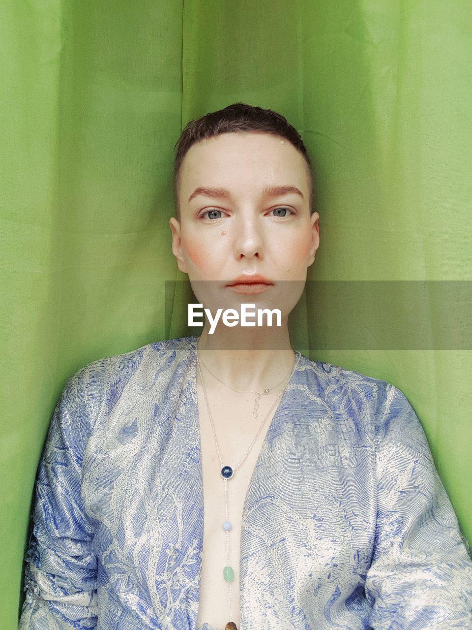 Portrait of woman against curtain