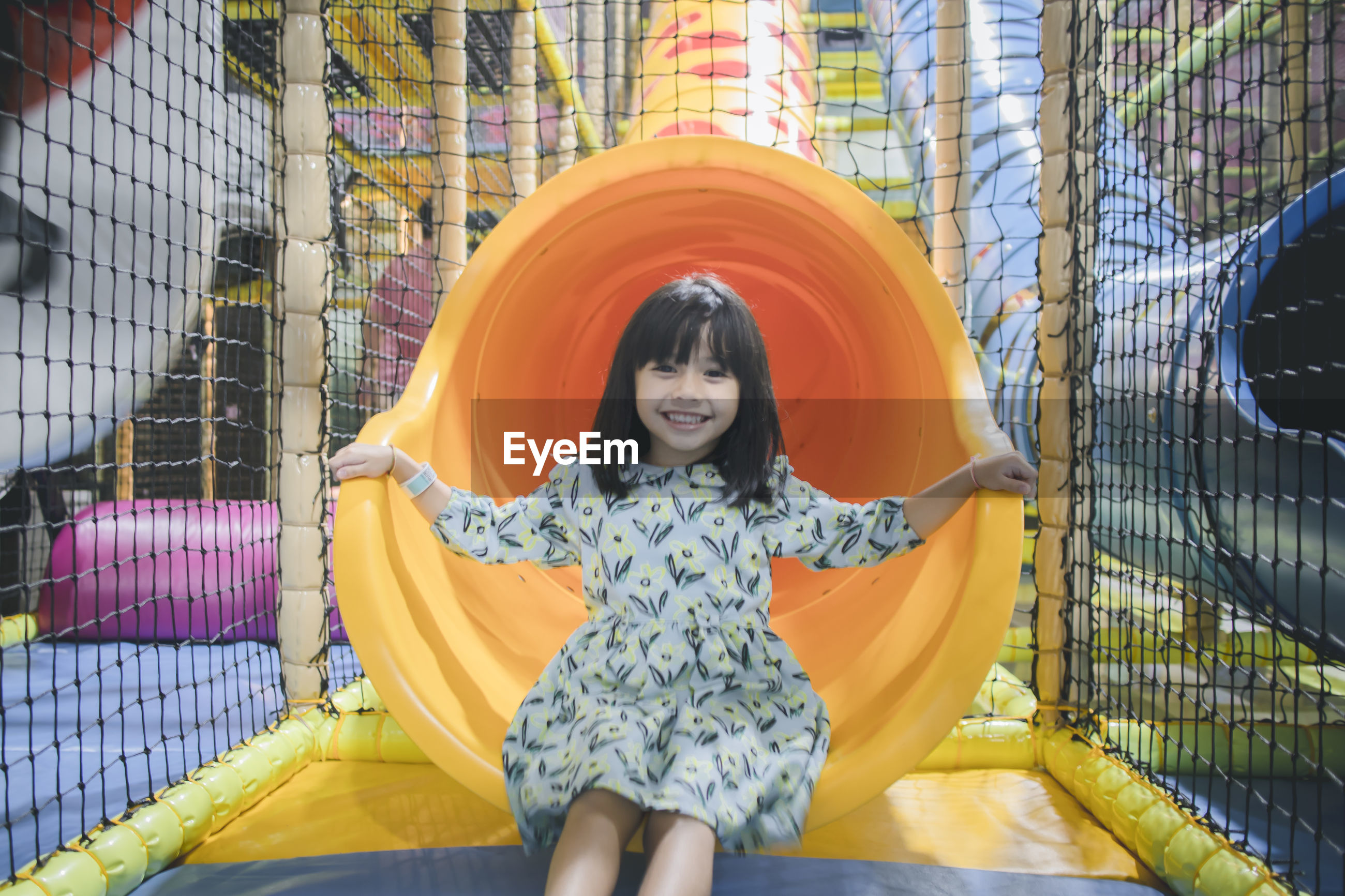 Portrait of smiling innocent girl sitting in slide